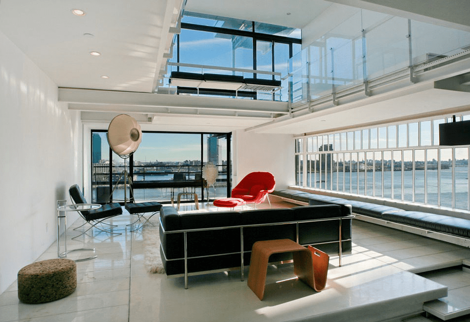 This is the spacious and airy living room with a large L-shaped black sofa that contrasts the bright white floor, walls and ceiling brightened by the glass walls. Image courtesy of Toptenrealestatedeals.com.