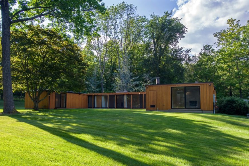 This is a look at the back of the U-shaped house with lots of glass walls that complement the wooden exteriors. These are then adorned with a lush landscaping of grass lawns and tall trees. Image courtesy of Toptenrealestatedeals.com.