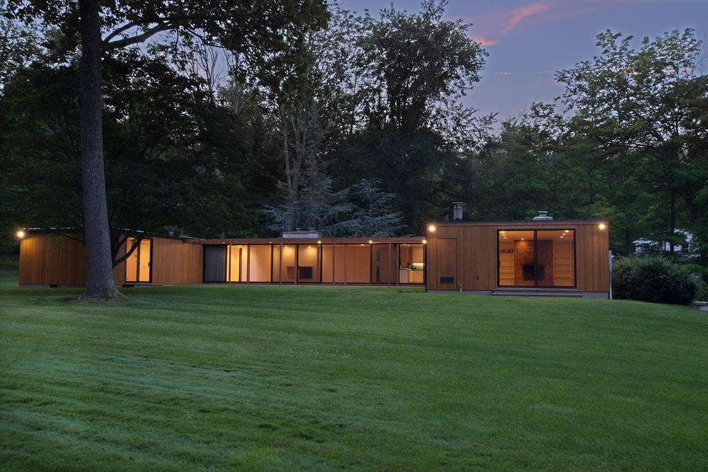 This is a nighttime look at the back of the house showcasing the glass walls that glow warmly from the interior lights. Image courtesy of Toptenrealestatedeals.com.