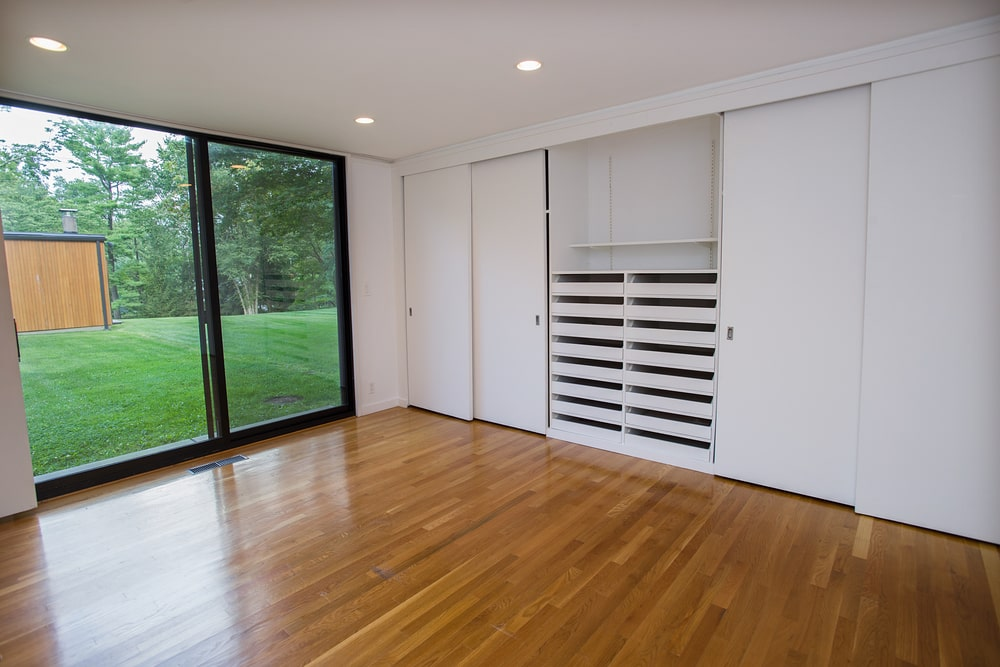 This is the bedroom with hardwood flooring and a large glass door leading to the outdoor area. One wall is dominated by a built-in cabinet with shelves and racks for shoes. Image courtesy of Toptenrealestatedeals.com.