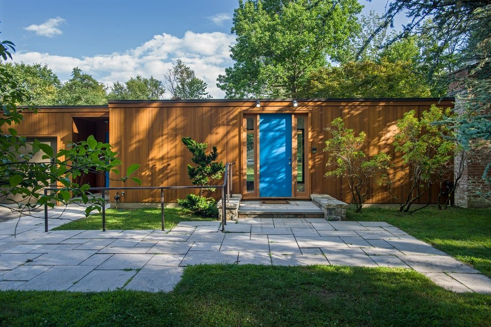 This is a closer look at the front of the house showcasing the main entrance with a blue door that stands out against the wooden exteriors. Image courtesy of Toptenrealestatedeals.com.