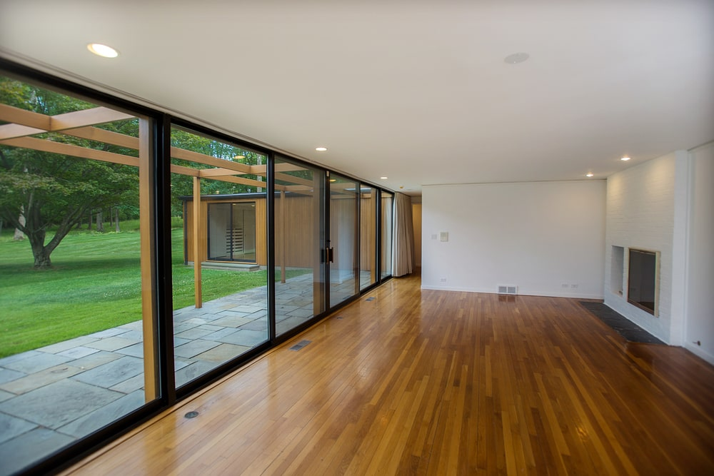 This is the great room with large glass walls that slide to open to the outdoor area. This spacious area can accommodate a living room area and a dining area easily. Image courtesy of Toptenrealestatedeals.com.