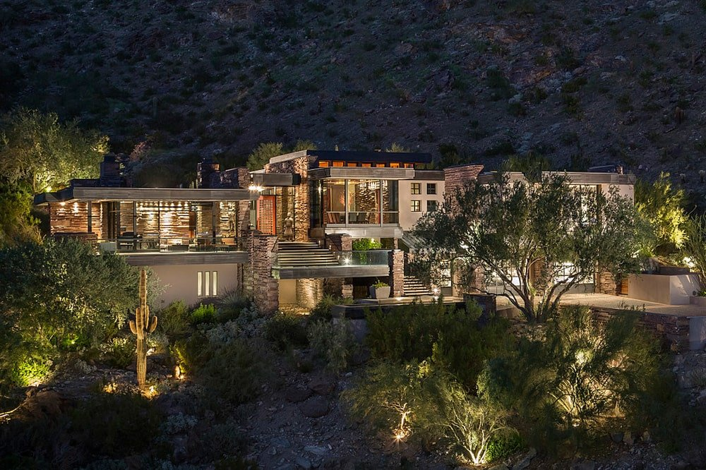 This is an aerial view of the front of the house of this mountainside mansion. Here you can see that the warm glow of the interiors match well with the outdoor lights as well as the lighting of the surrounding landscape.