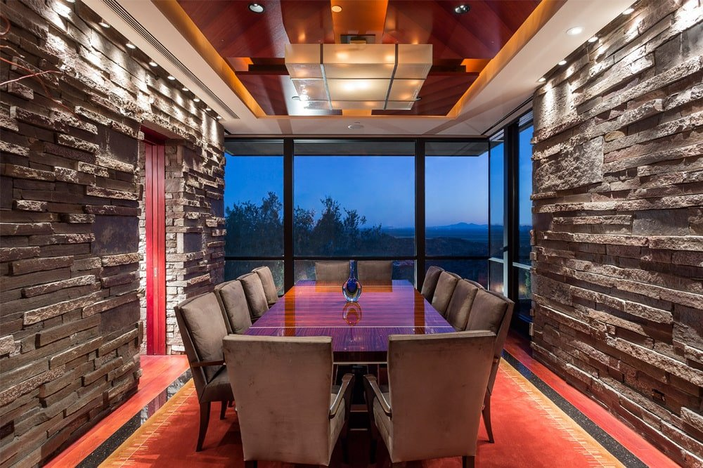 This is the formal dining room with a large rectangular dining table and glass walls that offer a view of the surrounding landscape. Image courtesy of Toptenrealestatedeals.com.