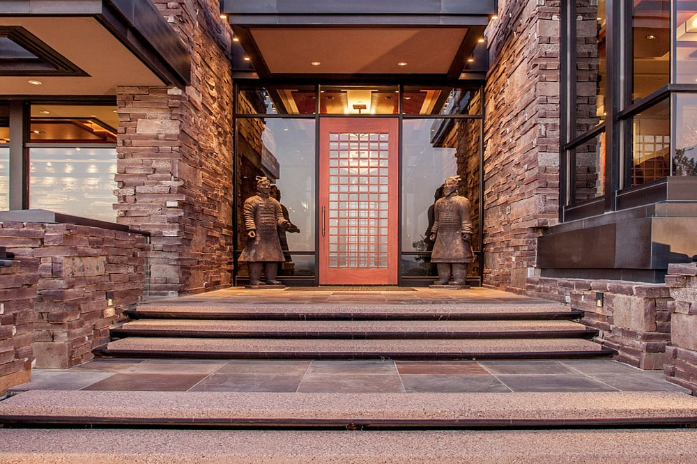 This is a look at the main entrance of the house with a door flanked by oriental decorative statues. Image courtesy of Toptenrealestatedeals.com.