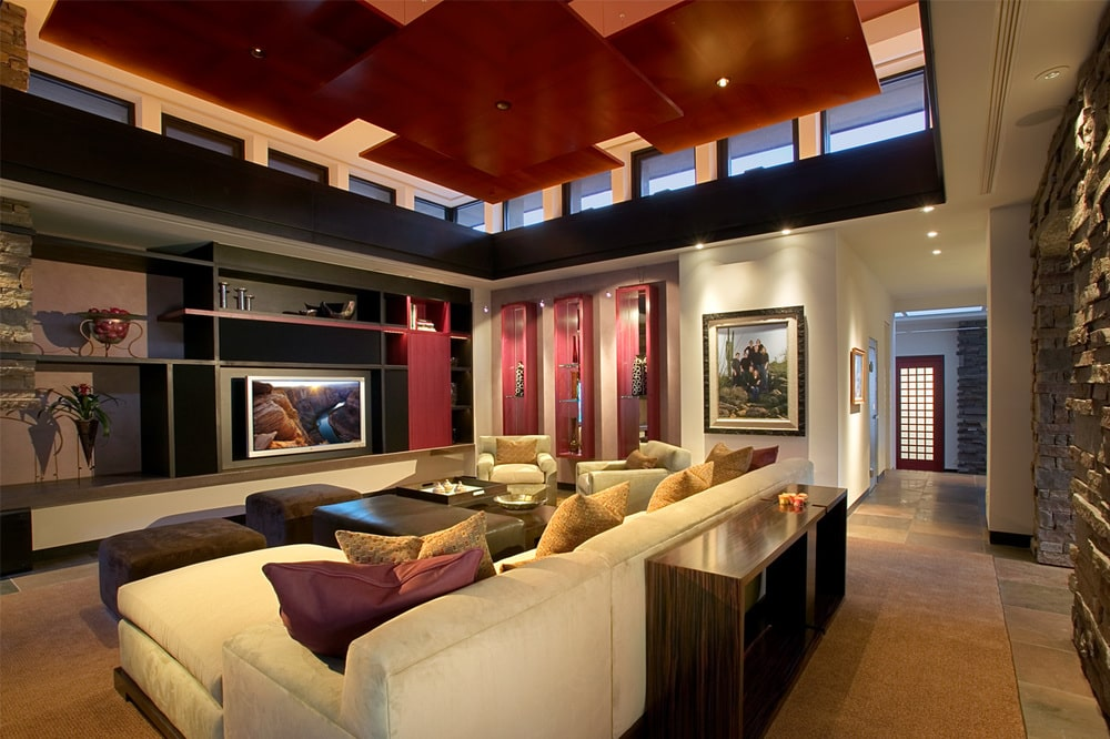 The family room has a large L-shaped sectional sofa under a wooden ceiling illuminated by the rows of transom windows. Image courtesy of Toptenrealestatedeals.com.
