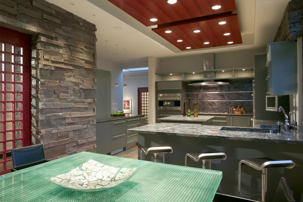 The kitchen has a breakfast bar as well as an informal dining area under a tray ceiling with recessed lights. Image courtesy of Toptenrealestatedeals.com.