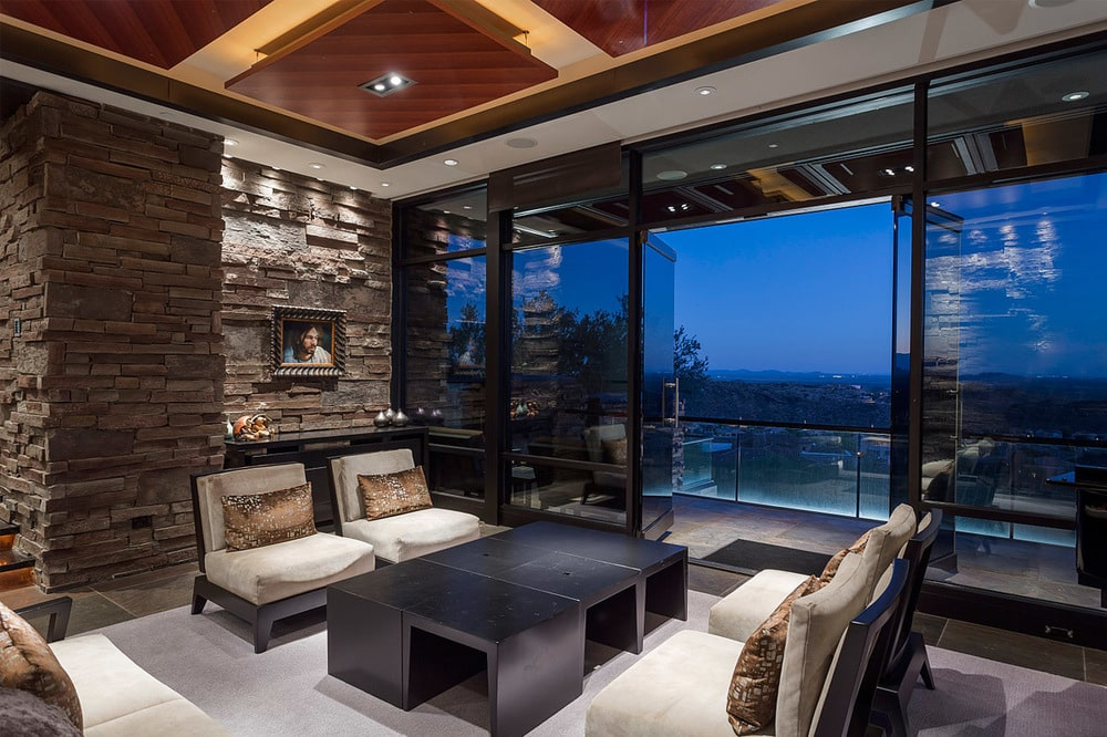 The living room has pairs of cushioned chairs and a coffee table next to the sliding glass doors that offer a view of the terrace. Image courtesy of Toptenrealestatedeals.com.