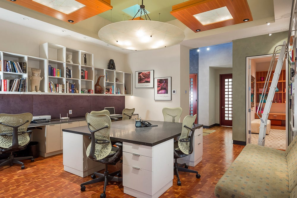 The home office has a large desk that can sit up to four people. On the far wall is a built-in cabinet and shelf that also serves as a desk. Image courtesy of Toptenrealestatedeals.com.