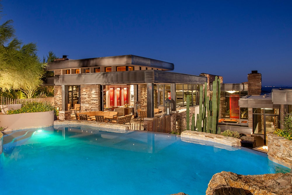 This is a view of the pool and the poolside patio surrounded by landscaping that has various plants and rocks. Image courtesy of Toptenrealestatedeals.com.
