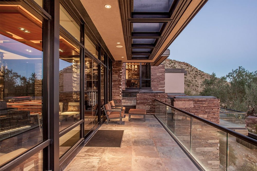 This is the terrace just outside the sliding glass doors. This area is fitted with cushioned armchairs and glass railings to maximize the view. Image courtesy of Toptenrealestatedeals.com.