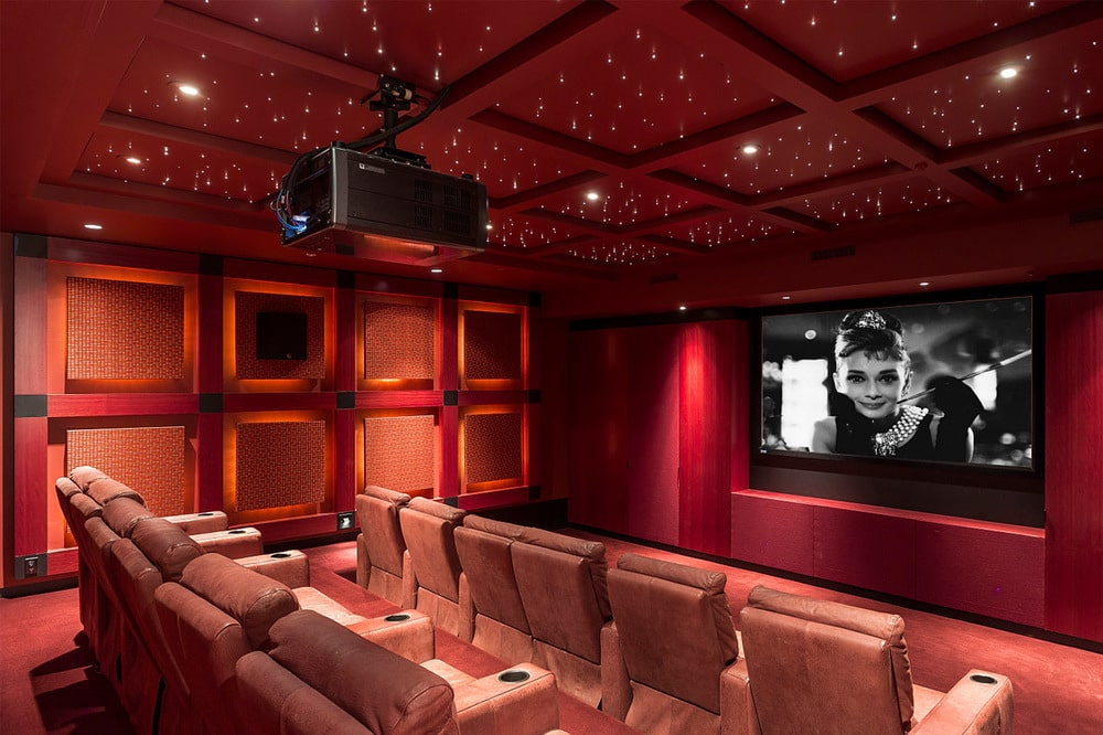 This is the home theater of the mansion with a wide screen on the far wall across from rows of upholstered theater chairs surrounded by red tones on the walls and coffered ceiling. Image courtesy of Toptenrealestatedeals.com.