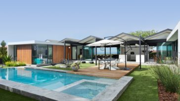 This is a look at the whole house from the vantage of the backyard pool. Here you can see the various glass walls and metal structures that give it a unique look. Image courtesy of Toptenrealestatedeals.com.