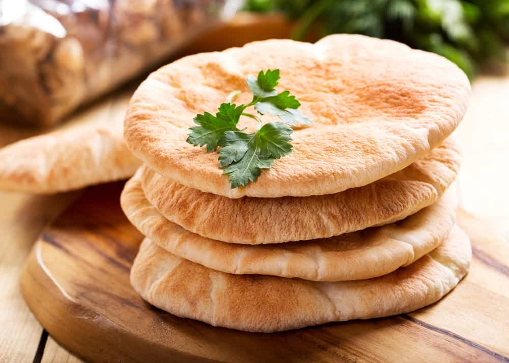 Stacked pita bread over a wooden board.