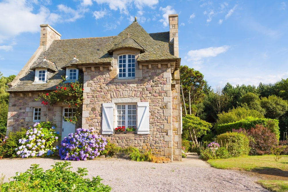 A house with a pretty exterior and a beautiful garden.