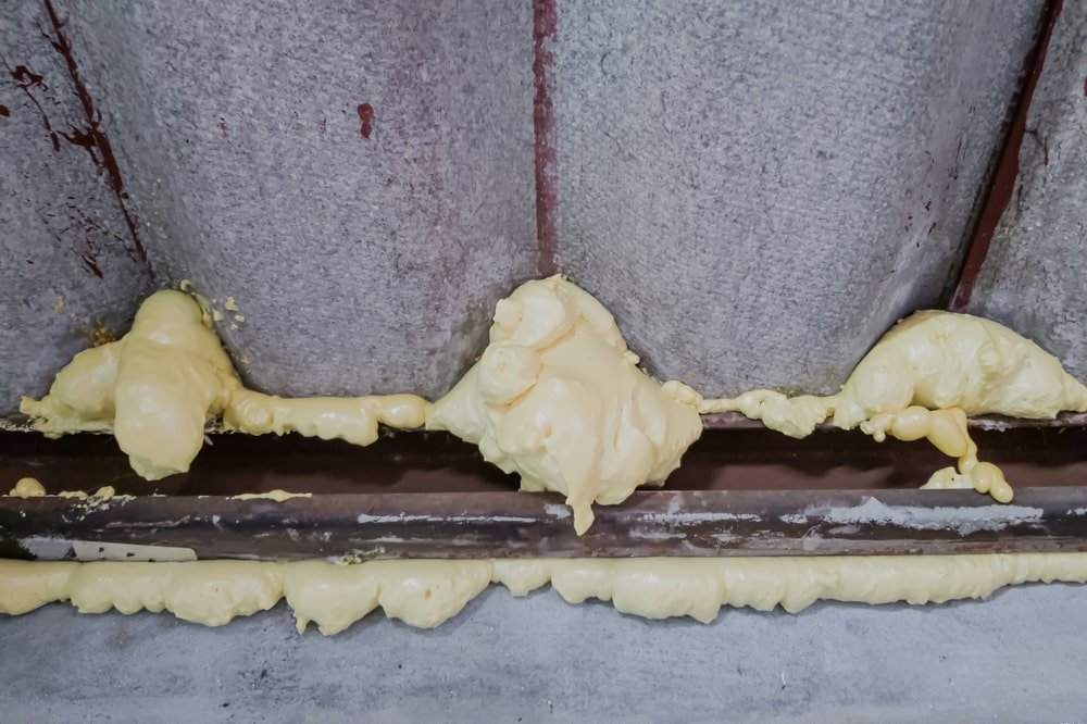 A close look at a wall with insulation maintained with foam sealant.