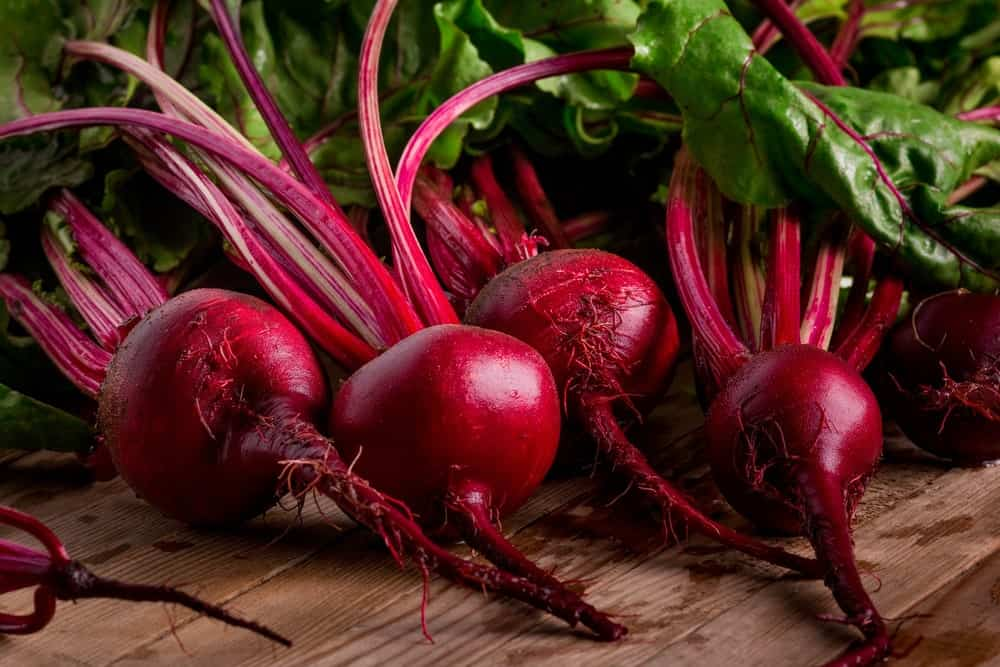 Red beets on a wooden table.