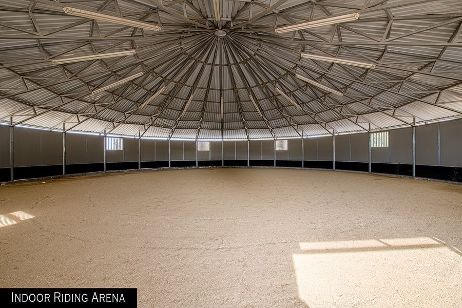 This is the indoor riding arena with a large circular dome with sand on the floor. Image courtesy of Toptenrealestatedeals.com.