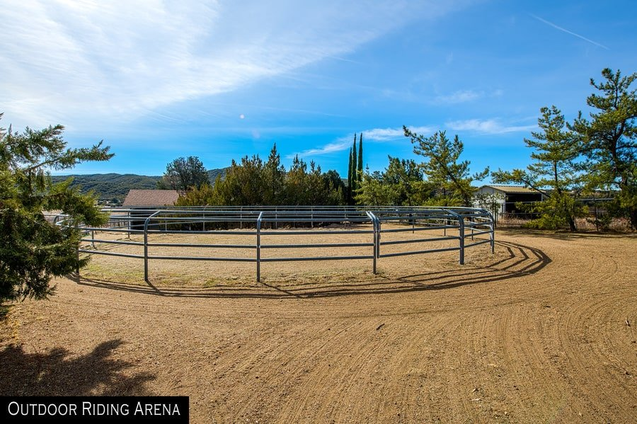 The outdoor riding arena has sand and iron fencing surrounding it. Image courtesy of Toptenrealestatedeals.com.