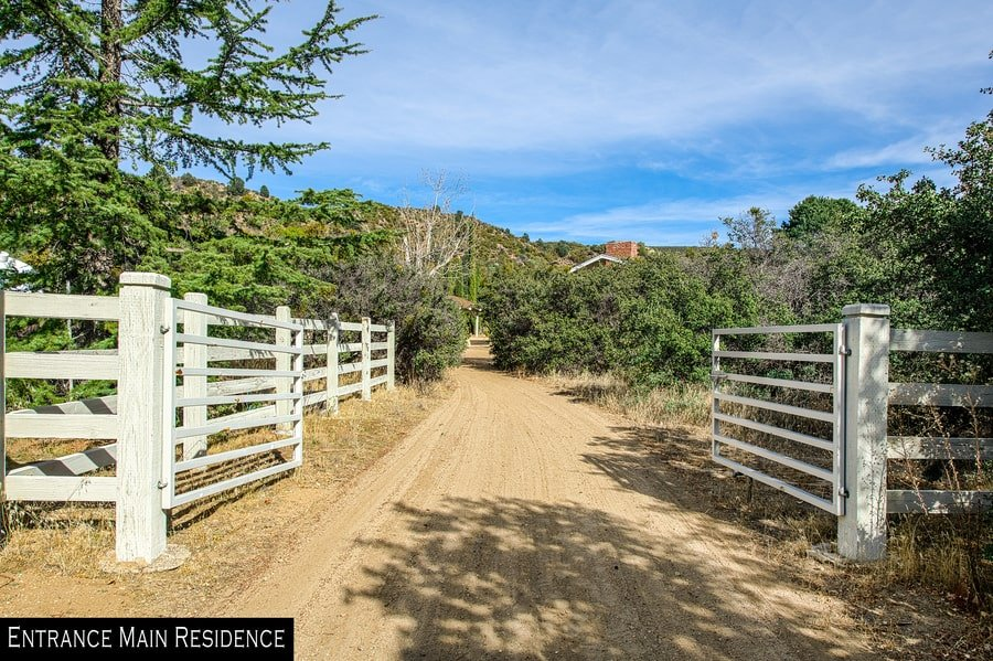 This is the driveway and gate that leads to the main house of the ranch adorned with tall trees and shrubs. Image courtesy of Toptenrealestatedeals.com.