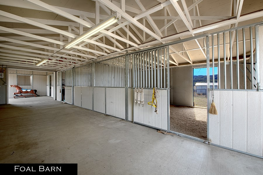 This is the foal barn with multiple stalls for the growing foal under a large cathedral ceiling with exposed beams. Image courtesy of Toptenrealestatedeals.com.