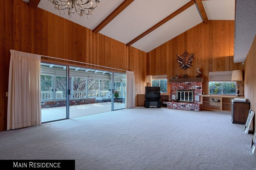 This is the spacious living room with a red brick stone fireplace at the far end that pairs well with the wood-paneled walls topped with a tall cathedral ceiling. Image courtesy of Toptenrealestatedeals.com.