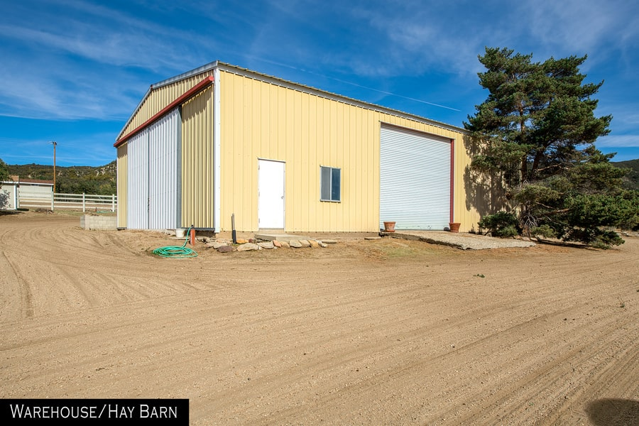 This is a look at the exterior of the warehouse and hay barn with bright beige walls and large doors that can fit trucks. Image courtesy of Toptenrealestatedeals.com.
