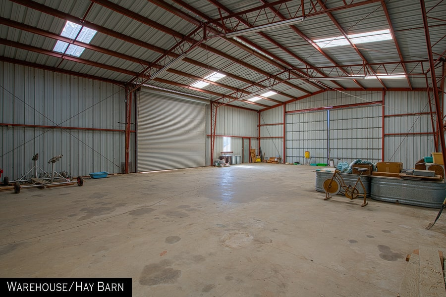 This is a look at the interior of the large warehouse and hay barn. It has a large space with a concrete floor. Image courtesy of Toptenrealestatedeals.com.