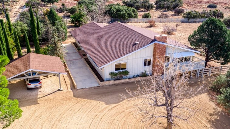 This is an aerial view of the main house of the ranch. It has white exterior walls with terracotta roof that matches with the surrounding land adorned by shrubs and trees. Image courtesy of Toptenrealestatedeals.com.