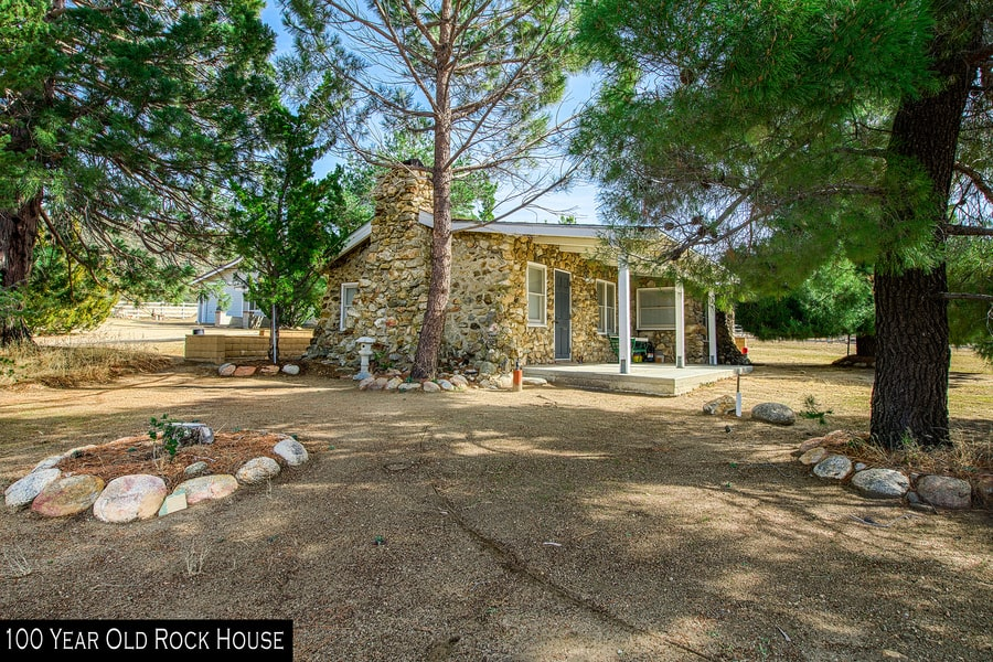 This is the stone house of the ranch that is over a hundred years old. Here you can see the stone walls of the exterior with a stone chimney. Image courtesy of Toptenrealestatedeals.com.