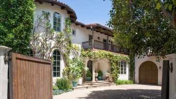 This is a look at the front of the house from the vantage of the main gate. Here you can appreciate more of the Spanish-style exteriors of the house softened by landscaping and creeping plants on its walls. Image courtesy of Toptenrealestatedeals.com.