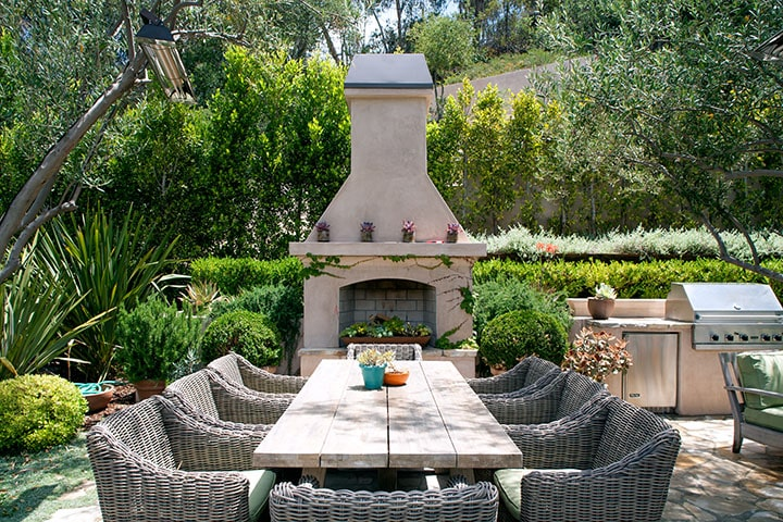 The outdoor dining area has a large rectangular dining table surrounded by woven wicker chairs. These are then complemented by the large outdoor fireplace by the head of the table. Image courtesy of Toptenrealestatedeals.com.