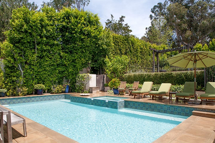 This is the pool area with beige stone walkways, lawn chairs and a background of tall walls, thick shrubs and hedges. Image courtesy of Toptenrealestatedeals.com.