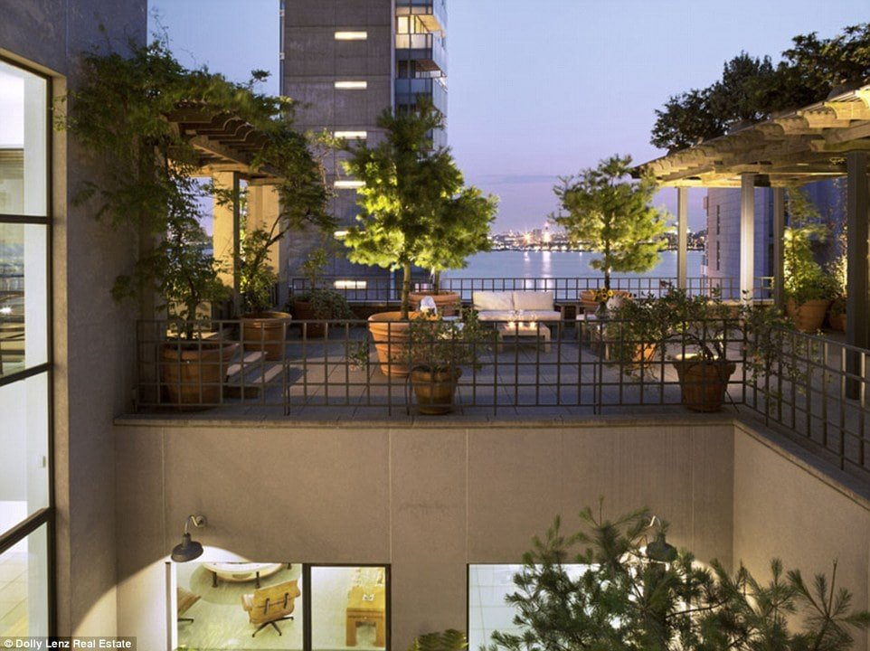 This is a nighttime view of the balcony with potted plants and a view of the city skyline. Image courtesy of Toptenrealestatedeals.com.