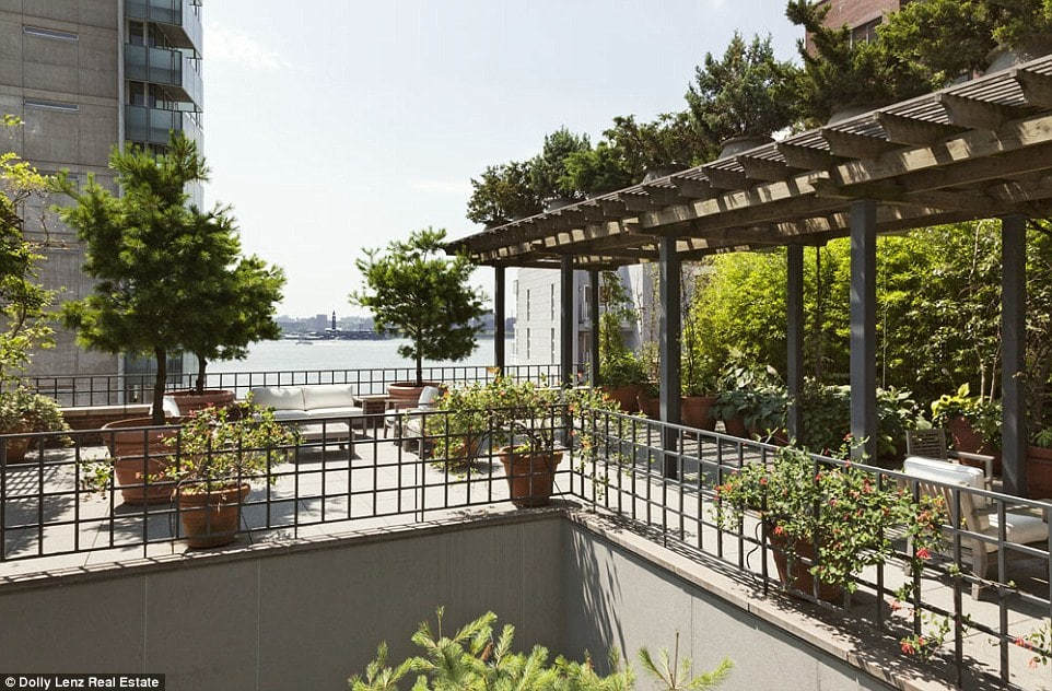This is balcony of the penthouse with an abundance of potted plants and shrubbery adorned with trellises. Image courtesy of Toptenrealestatedeals.com.