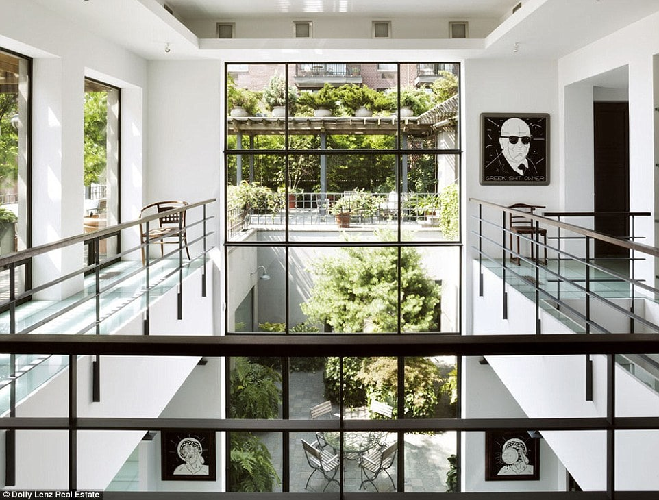 This is a view from the second level indoor balcony with wrought-iron railings that match the frames of the large glass wall on the far side. Image courtesy of Toptenrealestatedeals.com.