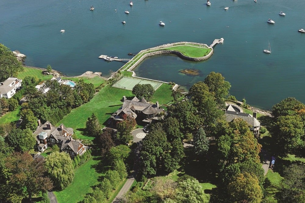 This is an aerial view of the property showing the earthy tone of the mansion standing out against the vast green landscape. You can also see here the tennis court by the water's edge. Image courtesy of Toptenrealestatedeals.com.