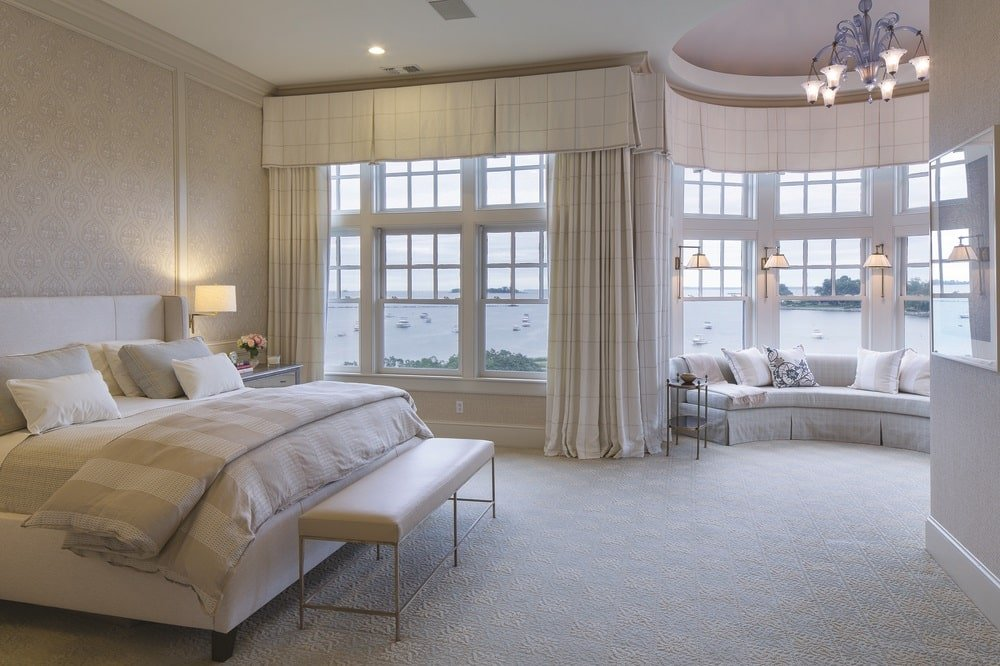 This is the primary bedroom with a large bed that blends well with the beige tone of the walls, floor and ceiling. The far wall has large windows fitted with a built-in bench for a reading nook. Image courtesy of Toptenrealestatedeals.com.