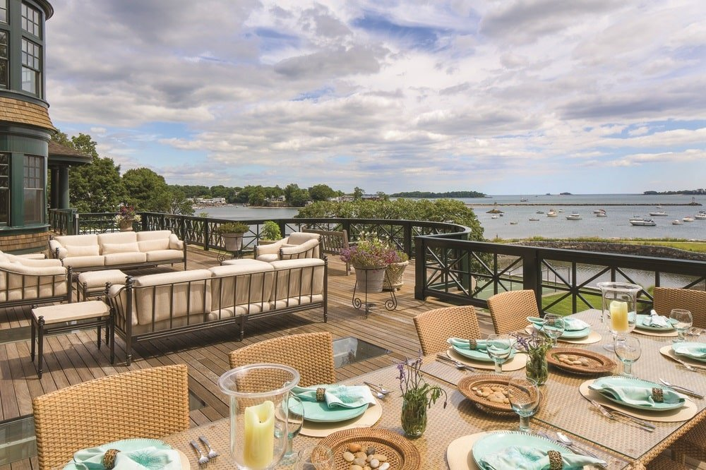 This is the viewing deck and terrace fitted with an outdoor dining set and a sofa set. The highlight of this area is the sweeping views of the water scene beyond. Image courtesy of Toptenrealestatedeals.com.