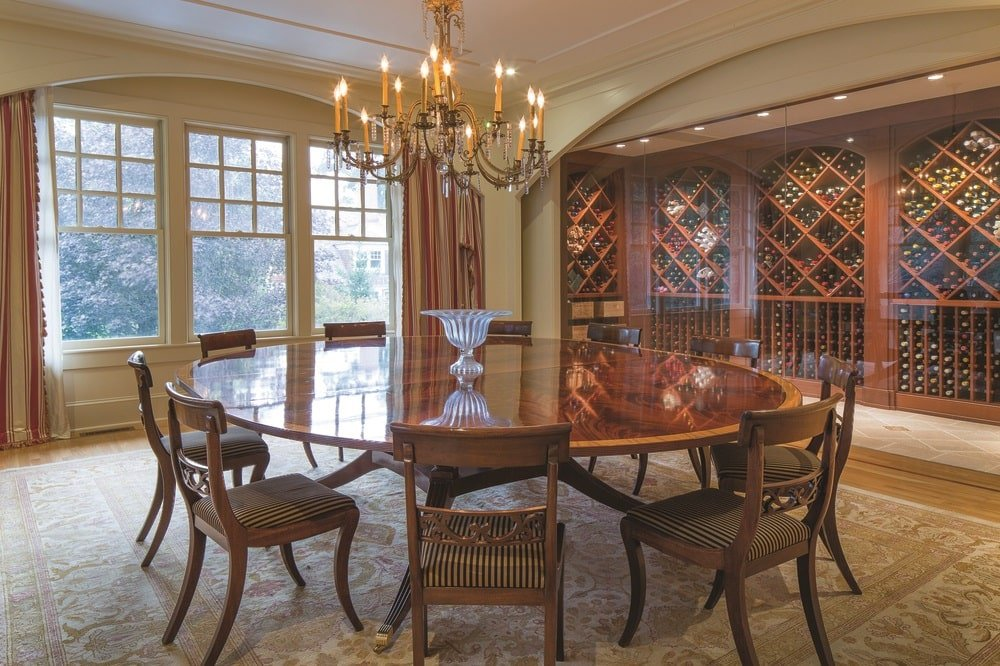 The formal dining room has a large dark wood dining table surrounded by matching chairs and topped with a chandelier from the beige ceiling. Image courtesy of Toptenrealestatedeals.com.