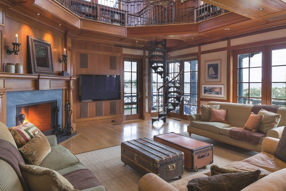 This other living room and family room has comfortable sofas surrounding a couple of wooden coffee tables across from the fireplace. Image courtesy of Toptenrealestatedeals.com.