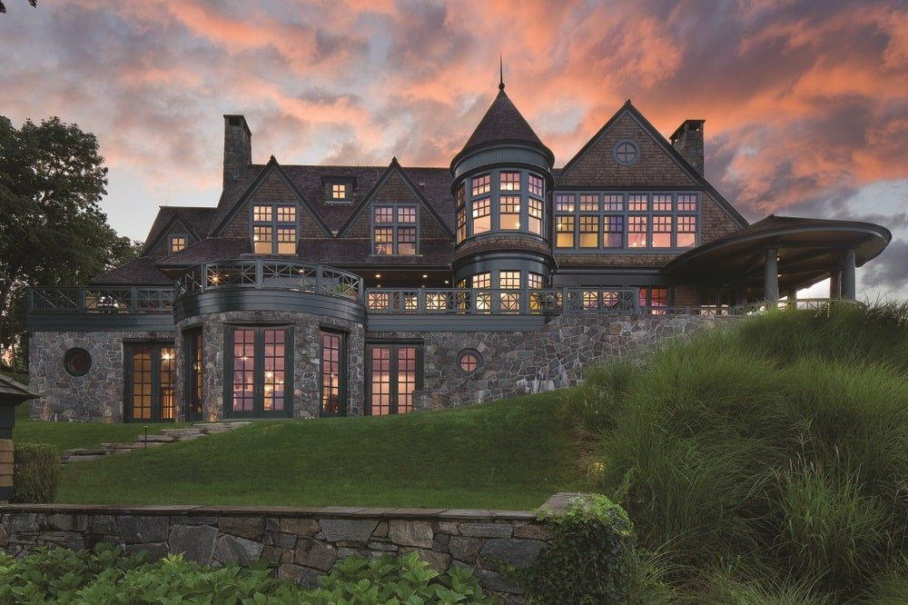 This is a front view of the mansion. You can see here the stone walls of the house complemented by the various glass windows that glow warmly from the interior lights. Image courtesy of Toptenrealestatedeals.com.