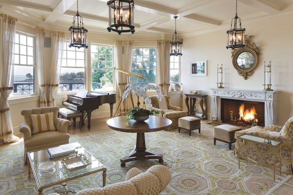 This is the living room with beige walls, beige coffered ceiling with lantern pendant lights and a fireplace at the far wall to warm the various chairs and the grand piano by the window. Image courtesy of Toptenrealestatedeals.com.