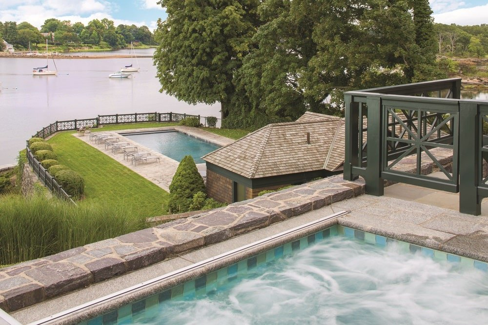 This is a look at the spa with a view over the backyard pool and the water beyond. These are complemented by the landscape of tall trees and well-manicured grass lawns. Image courtesy of Toptenrealestatedeals.com.
