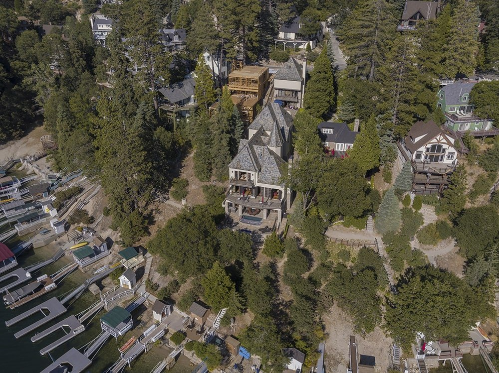 This aerial view shows the house and its surrounding thick foliage of tall trees that complement the exterior walls of the house. Image courtesy of Toptenrealestatedeals.com.