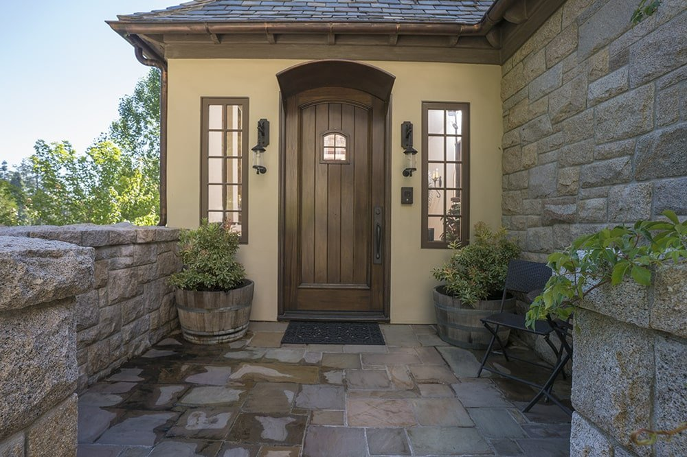 This is a closer look at the back entrance with a narrow dark wooden arched door flanked by sconces and side lights. Image courtesy of Toptenrealestatedeals.com.