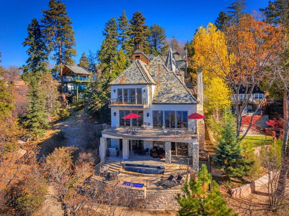 This is an aerial view of the back of the house. Here you can see the large windows and the exterior walls that are complemented by the surrounding tall trees. Image courtesy of Toptenrealestatedeals.com.