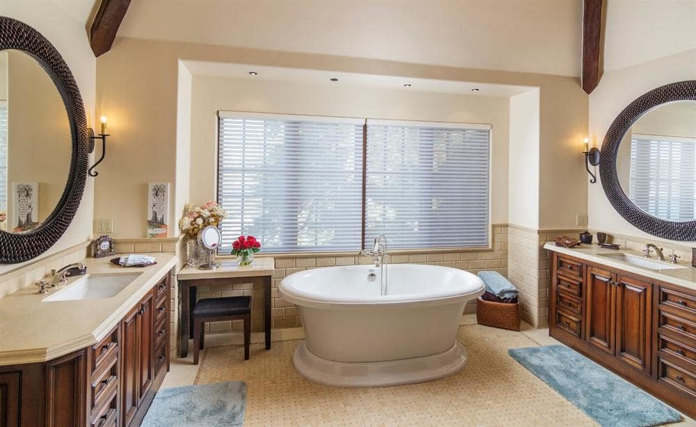 This bathroom shows the freestanding bathtub placed by the set of windows complemented by the flanking decors. Image courtesy of Toptenrealestatedeals.com.