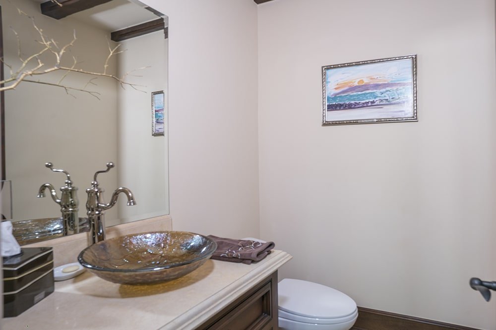 The toilet in this bathroom is place at the far corner beside the vanity. This is adorned with a wall-mounted painting. Image courtesy of Toptenrealestatedeals.com.