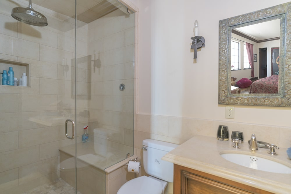 This other bathroom has a white porcelain toilet beside the glass-enclosed shower area on the far side with beige tiles. Image courtesy of Toptenrealestatedeals.com.